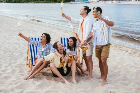 cheerful multicultural friends holding bottles of beer and sparklers while having fun on beach
