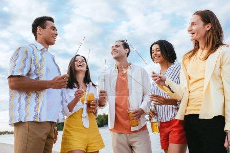 Foto de Amigos multiculturales felices sonriendo mientras sostiene chispas en la playa - Imagen libre de derechos
