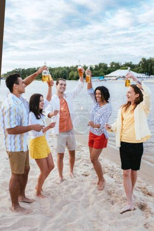 Photo for Smiling multicultural friends holding bottles of beer and sparklers while having fun on beach - Royalty Free Image
