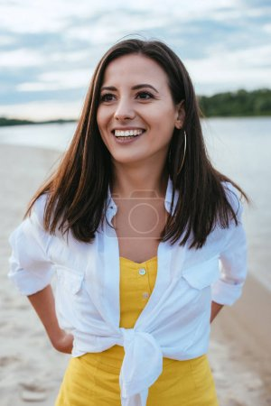 attractive, cheerful young woman looking away while standing on riverside