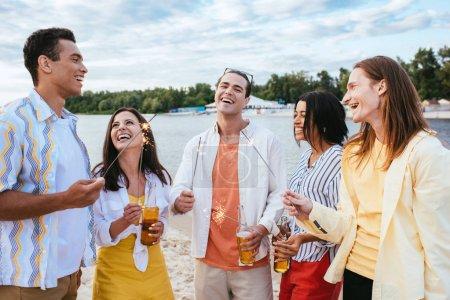 Foto de Amigos multiculturales felices sosteniendo botellas de cerveza y chispas mientras se divierten en la playa - Imagen libre de derechos