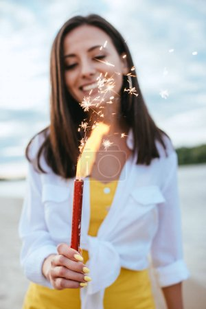 Photo for Selective focus of happy young woman holding sparkler while standing on beach - Royalty Free Image