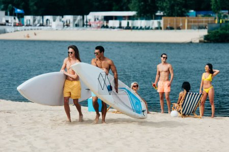 Photo for Handsome, young multicultural men holding surfing boards while walking on beach - Royalty Free Image