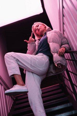 Photo pour Vue inférieure de la fille blonde élégante dans la veste en bas restant sur des escaliers et affichant le doigt moyen - image libre de droit