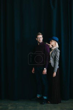 Photo pour Vue pleine longueur de jeune homme élégant dans des lunettes et femme blonde dans le chapeau près du rideau - image libre de droit
