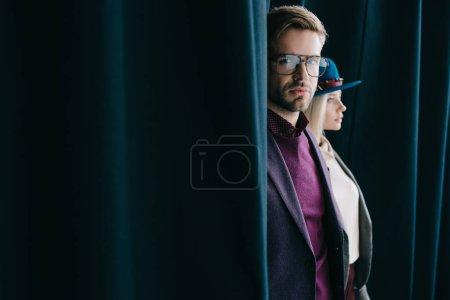 Photo pour Élégant jeune homme dans des lunettes et femme blonde dans le chapeau près du rideau - image libre de droit