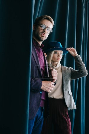 Photo for Stylish young man in glasses and blonde woman in hat near curtain - Royalty Free Image
