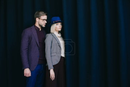 Photo for Elegant young woman in hat and man in glasses near curtain - Royalty Free Image