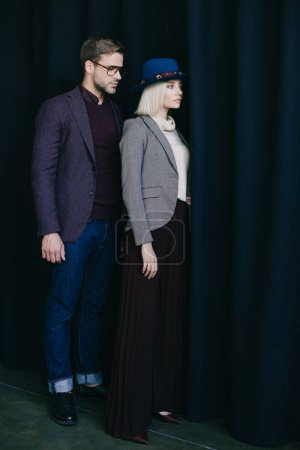 Photo for Full length view of elegant young woman in hat and man in glasses near curtain - Royalty Free Image