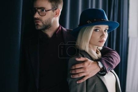 Photo pour Élégant jeune homme dans des lunettes embrassant fille blonde dans le chapeau près du rideau - image libre de droit