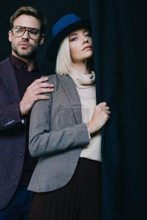 Photo pour Élégante jeune femme en chapeau et homme en lunettes près du rideau - image libre de droit