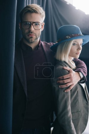 Photo for Elegant young man in glasses embracing blonde girl in hat near curtain - Royalty Free Image