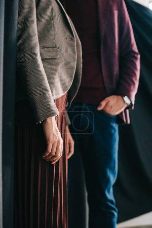Photo pour Vue recadrée de jeune femme et d'homme élégant restant avec la main dans la poche près du rideau - image libre de droit