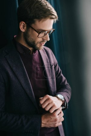 Photo for Stylish young man in jacket and glasses standing near curtain - Royalty Free Image