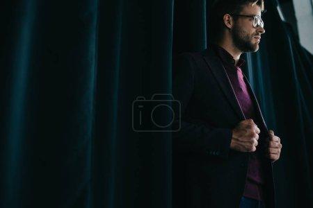 Photo pour Élégant jeune homme en veste et lunettes debout près du rideau et regardant loin - image libre de droit