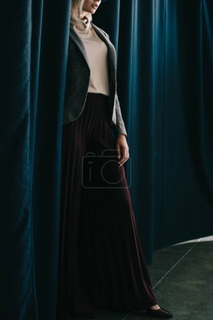 Photo for Cropped view of elegant woman in palazzo pants standing near curtain - Royalty Free Image