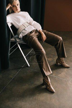 Photo pour Femme blonde élégante dans le chemisier blanc et les bottes avec l'impression de peau de serpent s'asseyant sur la présidence près du rideau sur le brun - image libre de droit