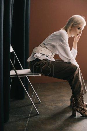 Photo pour Vue de côté de la femme blonde élégante dans le chemisier blanc et les bottes avec l'impression de peau de serpent s'asseyant sur la présidence près du rideau sur le brun - image libre de droit