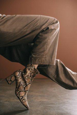 Photo pour Vue partielle de la femme en pantalon et bottes avec imprimé peau de serpent sur brun - image libre de droit