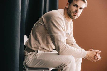 Photo pour Homme en tenue décontractée assis sur une chaise avec les mains serrées près du rideau sur brun - image libre de droit
