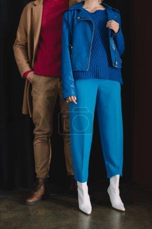 Photo pour Vue partielle de l'homme élégant dans le manteau et la femme dans la veste en cuir restant près du rideau - image libre de droit