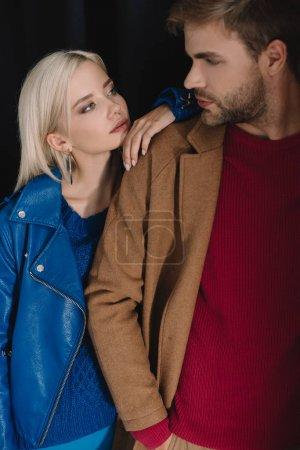 Photo pour Fille blonde et homme barbu dans les tenues d'automne regardant l'un l'autre sur le noir - image libre de droit