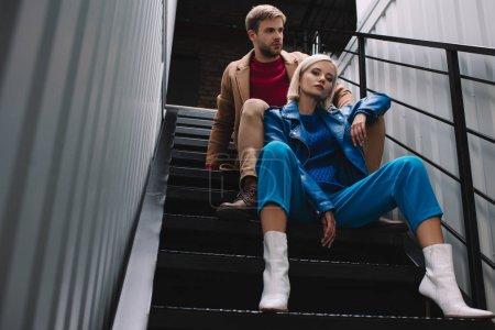 Photo pour Vue inférieure de jeune femme et homme élégants dans des vêtements d'automne se reposant sur des escaliers - image libre de droit