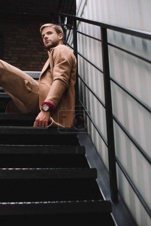 Photo pour Homme pensif dans le manteau brun s'asseyant sur des escaliers et regardant loin - image libre de droit