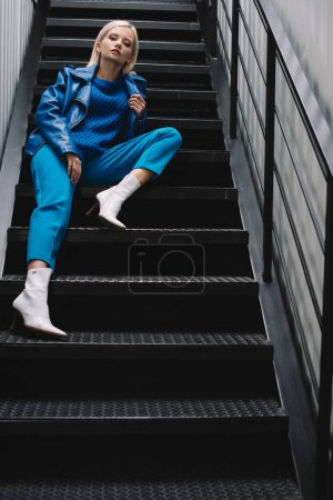 Photo for Blonde woman wearing blue leather jacket and heels sitting on stairs - Royalty Free Image