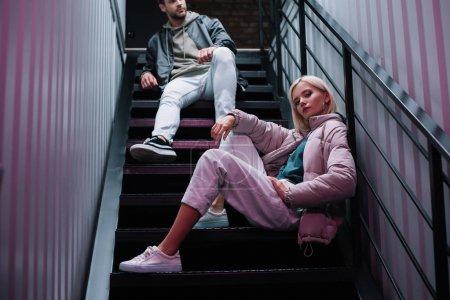Ausgeschnittener Blick auf stilvolle junge Männer und Frauen im lässigen Herbst-Outfit auf der Treppe