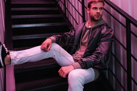 Photo pour Cher jeune homme barbu en veste assis sur les escaliers - image libre de droit