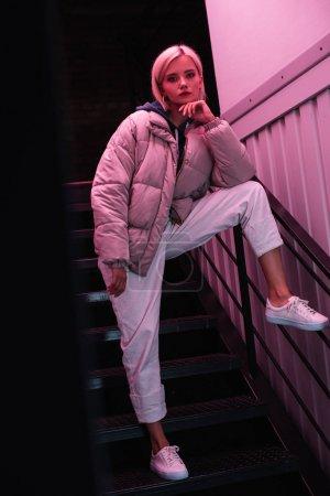 Ansicht des stilvollen blonden Mädchens in Daunenjacke, das auf der Treppe steht und in die Kamera schaut