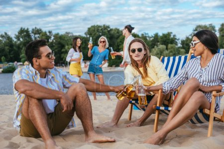 cheerful multiethnic friends clinking bottles of beer while having fun on beach