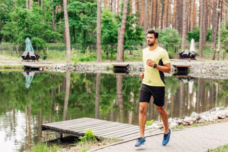 handsome sportsman running on walkway near lake