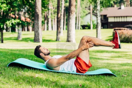 Photo for Side view of sportsman with closed eyes doing do abs on fitness mat outside - Royalty Free Image