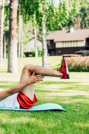 Photo pour Vue recadrée de sportif faisant l'exercice sur le tapis de forme physique - image libre de droit