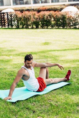 Photo pour Beau sportif barbu faisant l'exercice sur le tapis de forme physique - image libre de droit
