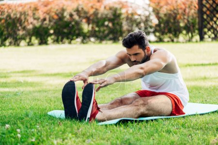 Photo for Handsome sportsman doing stretching exercise on fitness mat - Royalty Free Image