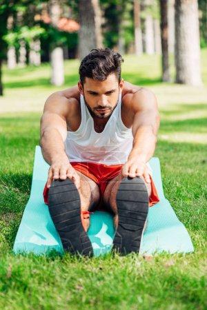 Photo pour Foyer sélectif du beau sportif faisant l'exercice d'étirement sur le tapis de forme physique - image libre de droit