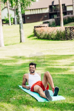 Photo for Happy sportsman lying on fitness man in park - Royalty Free Image