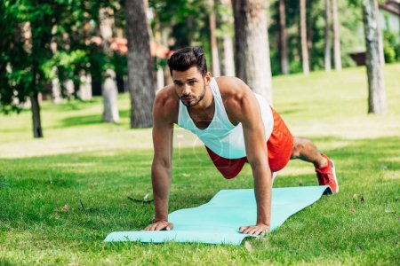 Photo for Handsome man doing plank exercise on fitness mat - Royalty Free Image