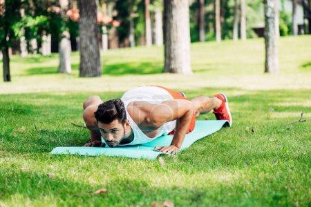 Photo pour Beau homme athlétique faisant push ups sur le tapis de fitness - image libre de droit