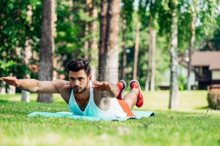 Photo pour Foyer sélectif de l'homme barbu beau travaillant dehors sur la pelouse - image libre de droit