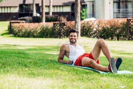 Photo pour Foyer sélectif de l'homme joyeux couché sur tapis de fitness à l'extérieur sur la pelouse - image libre de droit