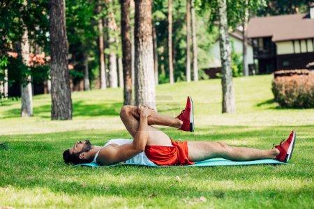 Photo pour Profil de l'homme athlétique barbu travaillant sur tapis de fitness dans le parc - image libre de droit