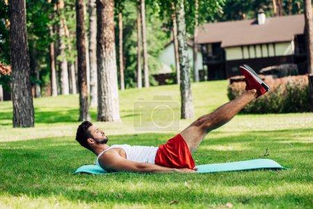 Photo pour Profil de bel homme athlétique travaillant sur tapis de fitness dans le parc - image libre de droit