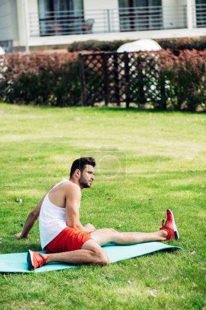 Brodaty sportowy człowiek siedzi na mat fitness w trawniku
