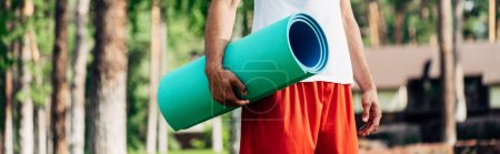 Photo for Panoramic shot of sportsman holding fitness mat in park - Royalty Free Image