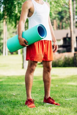 Photo for Cropped view of sportsman holding fitness mat while standing on grass - Royalty Free Image