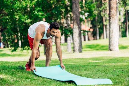 Photo pour Sportif heureux mettant tapis de fitness sur l'herbe dans le parc - image libre de droit